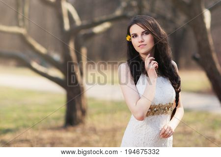 Pretty girl in white dress on blurred autumn background during photo shoot. Young beautiful woman with flowers in hair