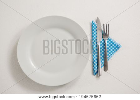 Overhead view of plate with eating utensils and napkin on table