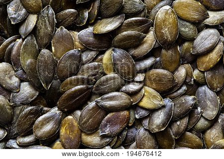 Green background of hulled pumpkin seeds.Textured effect.