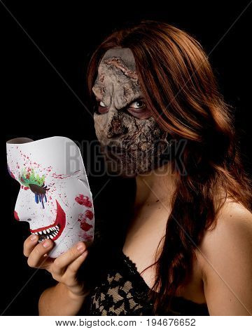 You don't want to meet the woman behind the mask. A halloween/horror character. Brunette female model with custom sculpted appliance and a black background