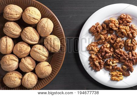 Walnuts whole and kernels in plate on dark wooden table top view