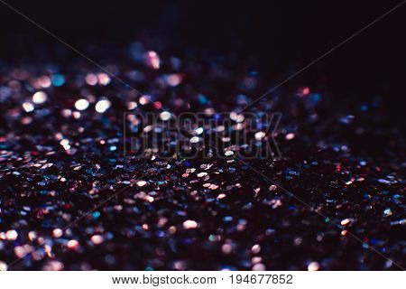 Abstract shining glitters violet makeup background. Blurred multicolored tinsel, selective focus with shallow depth of field. Glisten foil backdrop, christmas magic , eyeshadow closeup concept