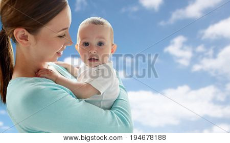 family, motherhood and parenthood concept - close up of happy smiling young mother with little baby over blue sky and clouds background