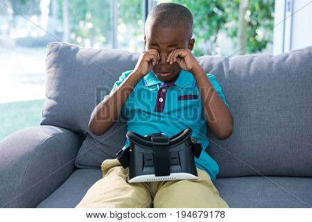 Boy rubbing eyes while sitting with VR headset on sofa in living room at home