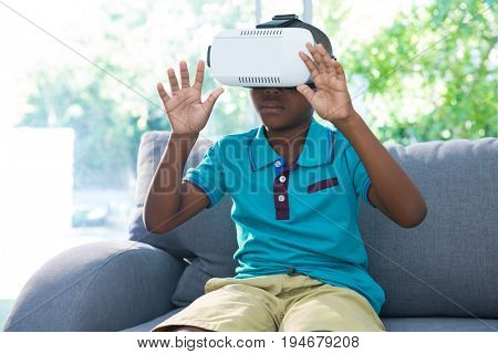 Boy wearing virtual reality headset with arms raised sitting on sofa at home
