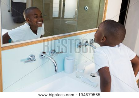 High angle view of boy clenching teeth while looking at mirror in domestic bathroom