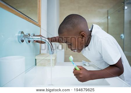 Side view of boy spitting while holding brush in sink at domestic bathroom
