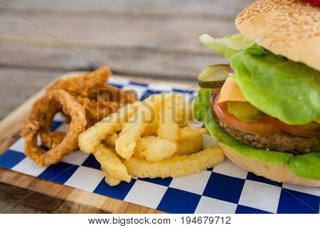Close up of onion rings and french fries with burger on cutting board