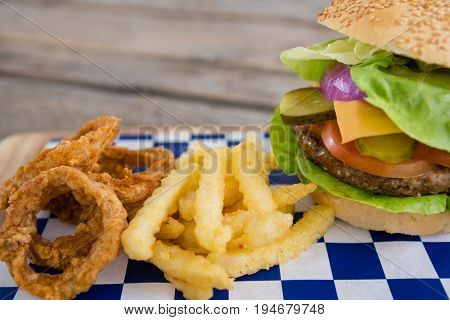 Close up of burger and onion rings with french fries on cutting board