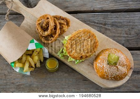 overhead view of burger with onion rings and french fries on table