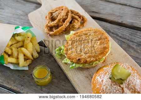 High angle view of burger with onion rings and french fries on cutting board at table