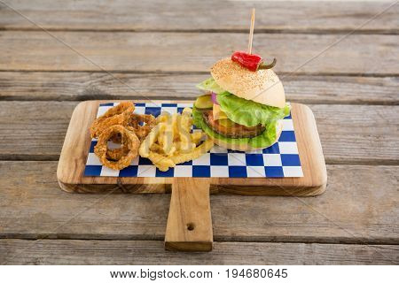 Hamburger with onion rings and french fries on cutting board at table