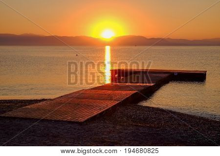 View on the sunrise on the sea the mountains and a wooden pier on the beach Moraitika island Corfu Greece.