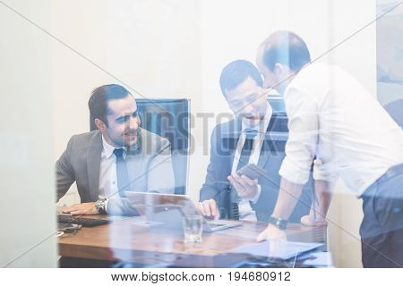 Cheerful corporate business people work in modern office. Project manager team solving a problem in relaxed healthy working environment. Business team looking at data at mobile phone monitor.