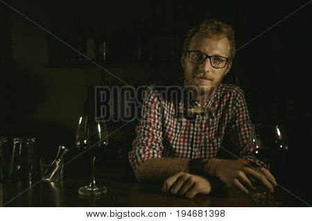 Man bartender holding wine glass at the bar  at the bar