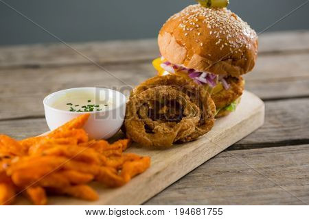 Close up of hamburger by onion rings with dip and french fries on cutting board