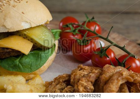 Close-up of hamburger, onion ring, cherry tomato and french fries on chopping board