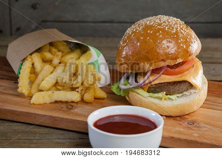 Close-up of hamburger, french fries and tomato sauce on table