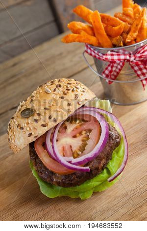 Close-up of hamburger and french fries on chopping board