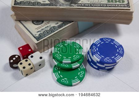Close-up of US dollars, dice and casino chips on white background