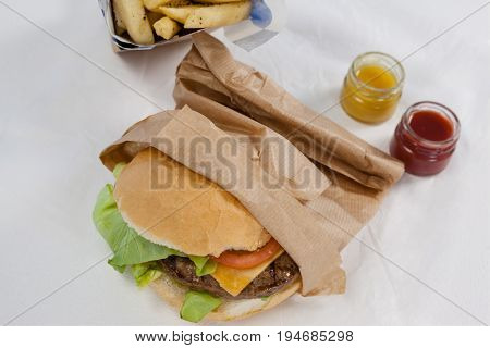 Overhead of hamburger in paper bag on table