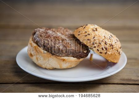 Close-up of hamburger in plate on wooden table