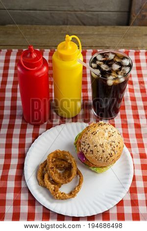 Close-up of hamburger, french fries, onion ring and cold drink on napkin