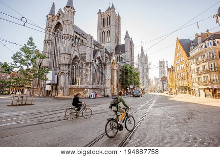 GENT, BELGIUM - June 02, 2017: CItyscape view on saint Nicholas church with people ride a bicycles during the morning in Gent old town, Belgium