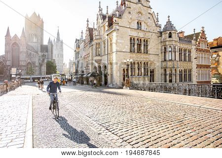 GENT, BELGIUM - June 02, 2017: Beautiful view on the old town with people walk on the saint Nicholas bridge during the sunrise in Gent city, Belgium