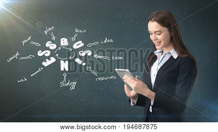 Beauty Woman In A Suit Holding Tablet Near Wall With Business Idea Sketch Drawn On It. Concept Of A
