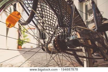 Rear wheel of a bicycle with an orange headlight. A black bicycle stands in the shadow of the building on a hot day. Tourism
