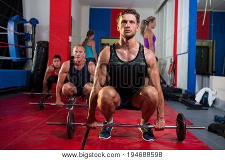 Young athletes crouching with barbells on exercise mat