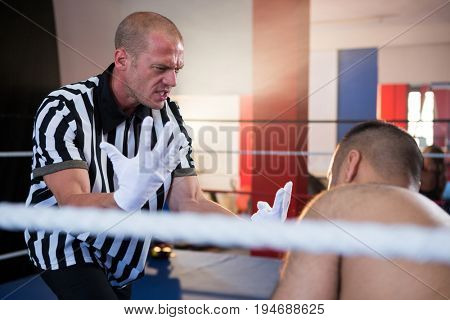 Referee gesturing to male boxer in boxing ring at fitness studio