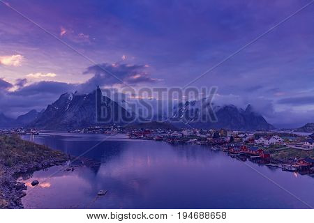 Reine on the Lofoten in northern Norway. The Typical Norwegian fishing village of Reine under midnight sun, blue sky, with the typical rorbu houses.  Mountain In Background