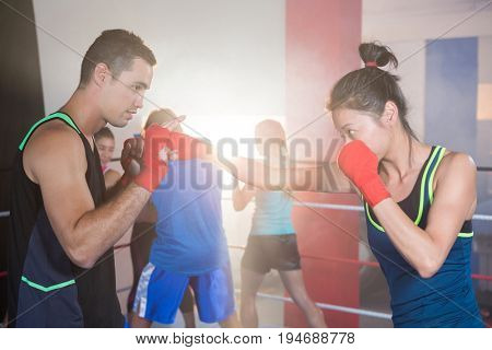 Young female boxer practicing punch with male in boxing ring