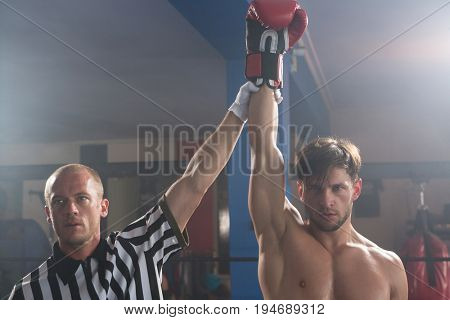 Referee holding hand of winning young male boxer in boxing ring at fitness studio