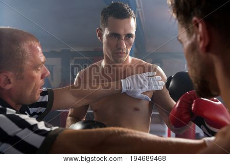 Referee stopping aggressive young male boxers in boxing ring