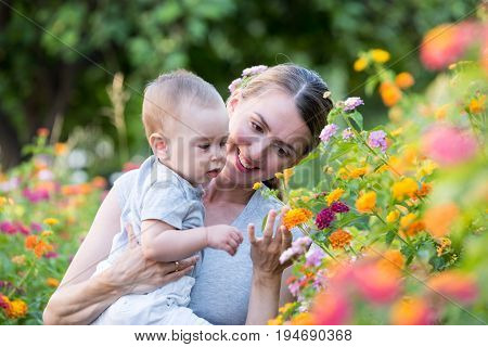Happy family outdoors. Mother holding her 8 month old little son and shows him beautiful blooming flowers in the garden. Curious child explores the world.