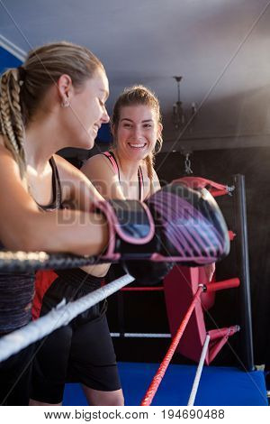 Trainee and coach interacting with each other in boxing ring