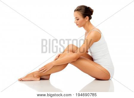 beauty, depilation, epilation, people and bodycare concept - beautiful woman touching her smooth bare legs over white background