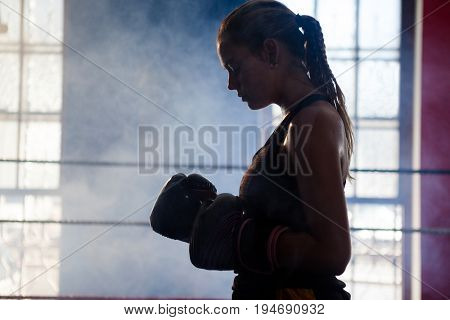 Determined woman standing in boxing ring in fitness studio