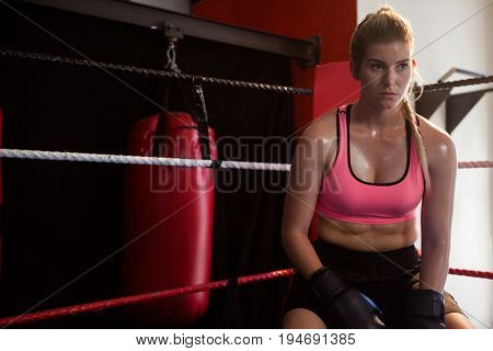 Thoughtful woman sitting in boxing ring at fitness studio