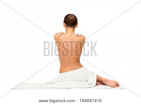 beauty, spa, people and bodycare concept - beautiful young woman in white towel with bare top