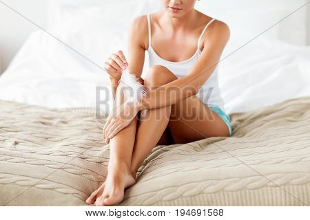 people, beauty, skincare and bodycare concept - beautiful woman sitting on bed and touching hand skin with feather at home bedroom