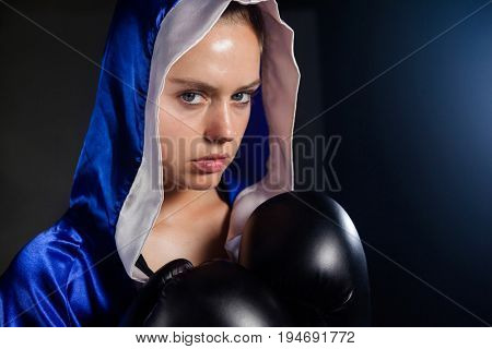Portrait of determined woman wearing boxing gloves
