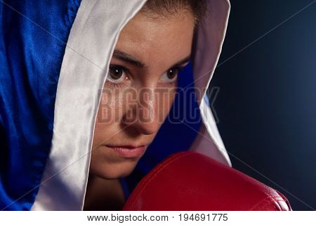 Determined woman wearing boxing robe in fitness studio