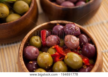 High angle view of olives in wooden container on place mat