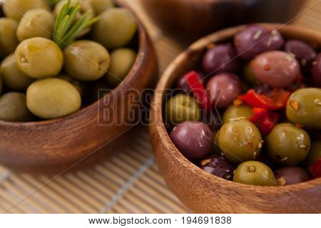 Close up of olives in wooden container on place mat