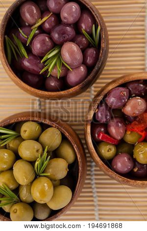 Directly above shot of olives in wooden bowls on place mat