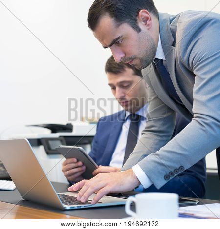 Image of two young businessmen solving business issue using laptop computer and touchpad at business meeting in moder office. poster